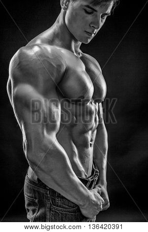 Muscular bodybuilder guy doing posing over black background. Naked torso in jeans. Close-up. Black and white, b w