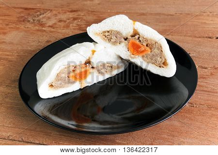 Bread split half show pork and salted egg on Black dish a wood plate background. And reflections on a plate.