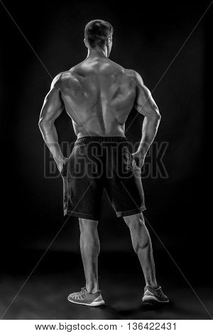 Muscular bodybuilder guy doing posing over black background. He turned his back. full height Black and white, b w