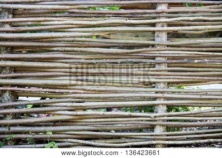 Wooden wicker fence made of sticks in the countryside.