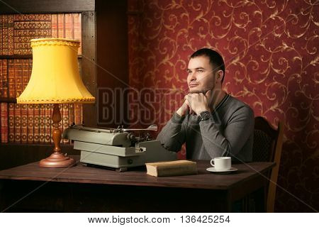 handsome writer with a typewriter in the interior