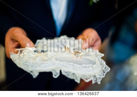 Two Wedding Rings On A Soft Pillow At Hands Of Witness