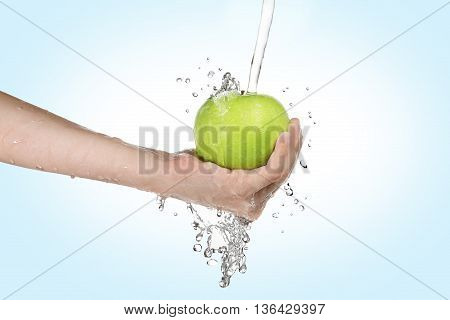 boy holding and washing a green apple