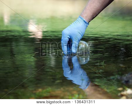 Water sample. Hand in glove collects water to explore. Concept - water purity analysis environment ecology. Water testing for infections permission to swim