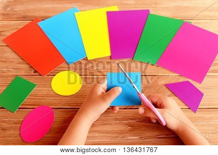 Child holds scissors and cardboard square in his hands. Colored cardboard sheets and different geometric figures on a wooden table. Child learns to cut paper shapes. Early childhood development