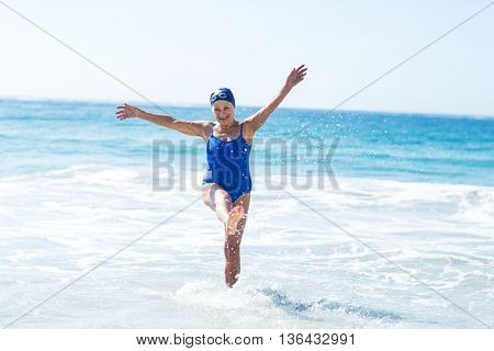Pretty mature woman playing on the beach on a sunny day