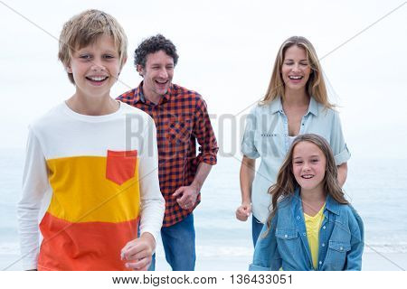 Happy family enjoying at beach against sky