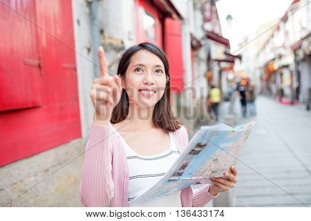 Woman looking at city guide in Macao city