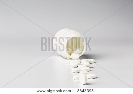 White plastic pill bottle and heap of round white pills