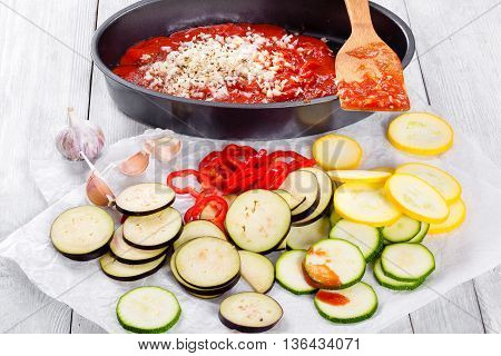 Raw ingredients for traditional French casserole ratatouille: zucchini red bell pepper onion yellow squash eggplant tomato sauce and garlic on a white parchment paper close-up