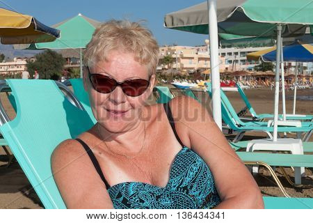 A woman of mature age in a swimsuit on a chaise longue on the beach