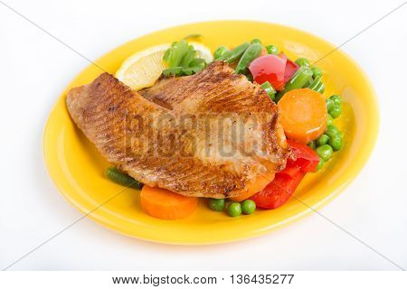 Fried fish fillet with vegetable garnish ona plate