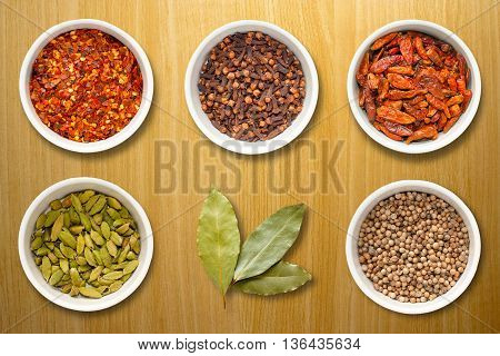 Spices including chilli flakes cloves bird's eye chillies cardamoms bay leaves and coriander seeds in white pots on a light pine work surface