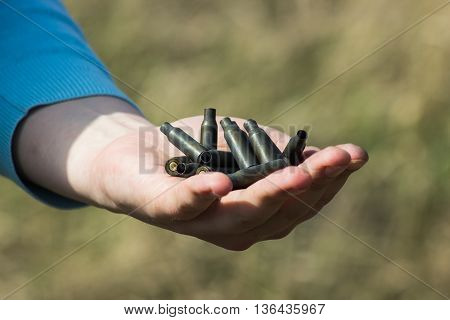man hand holding used shells on green