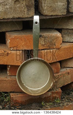 Iron scoop on brick wall under rain close up