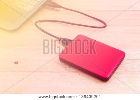 External hard drive for backup on wood background with soft focus color filtered background.