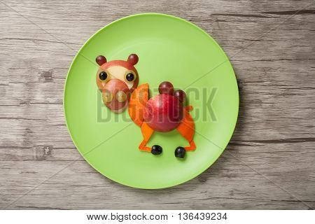 Camel made of fruits on plate and board