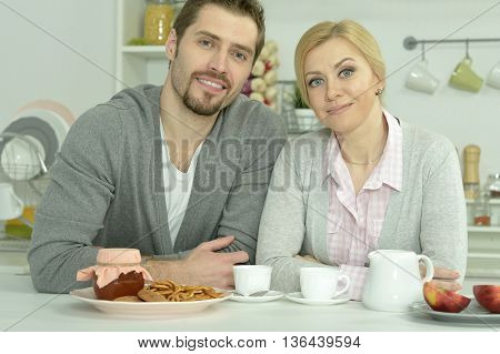 smiling couple at table with coffee and food