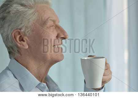 Portrait of a happy senior man with cup