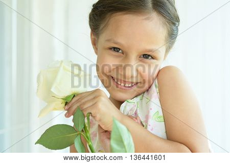 Portrait of adorable little girl with rose flower