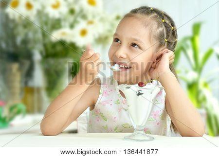 Portrait of little girl eating sweet  dessert with berries