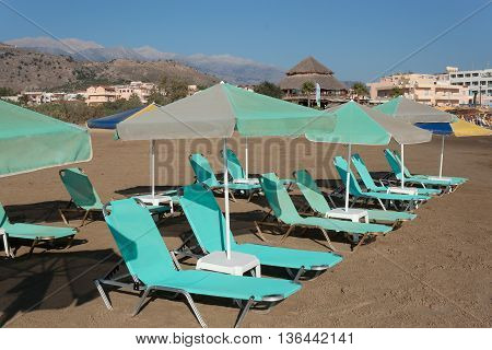 Rows of sun loungers and parasols on a sandy beach without people