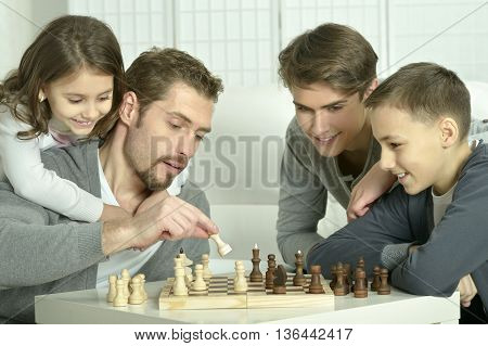 Family playing chess on a table at home