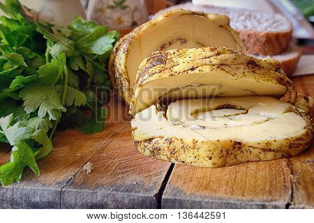 Cheese is cut by pieces on a wooden table. In the foreground cheese pieces. Sideways pieces of cheese are sprinkled spices. On the right greens lie. Indoors. Horizontal format. Color. Photo.