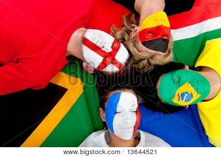 Football fans with painted faces lying on the South African flag - isolated over a white background