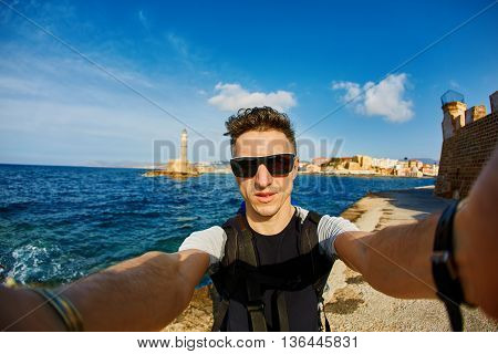 young man make selfie on the beach on the lighthouse and Chania bay background
