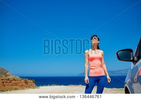 Happy woman enjoying freedom on travel in Crete coast, Greece. Female on summer or spring leisure vacation