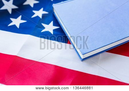 american independence day, patriotism and nationalism concept - close up of american flag and book