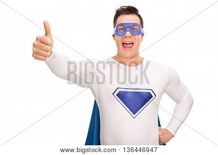 Joyful superhero giving a thumb up and looking at the camera isolated on white background