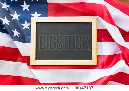 education, election, patriotism and nationalism concept - close up of blank school blackboard or chalkboard on american flag