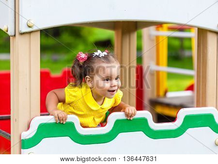 smiling little girl is playing in the park. She has fun on carousel