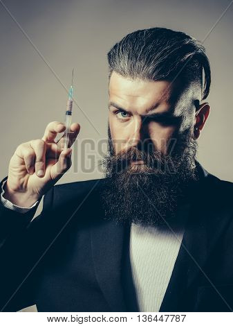 Handsome young man with long beard and moustache in black jacket holding syringe in studio on grey background