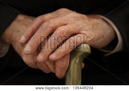 summer old hand that holds a wooden stick for support