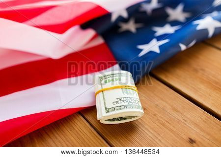 budget, finance and nationalism concept - close up of american flag and dollar cash money packet