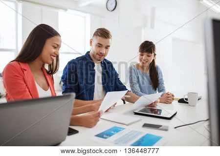business, startup, education and people concept - happy creative architect team or students with papers working at office
