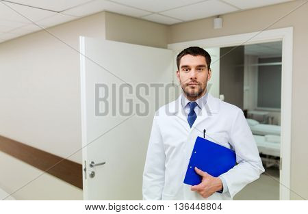 medicine, healthcare and people concept - doctor with clipboard at hospital
