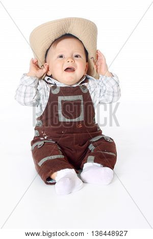 small kid in overalls sitting in full length and holds hands a hat white background, isolated
