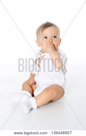 little kid in a white shirt and in a diaper, full-length sitting and sucking finger, white background, isolated