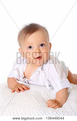 small kid in blouse lying on stomach and smiling at camera white background, isolated