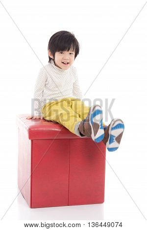 Cute asian boy sitting on red stool isolated