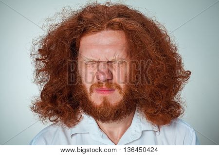 The young man with long red hair screwed up both eyes