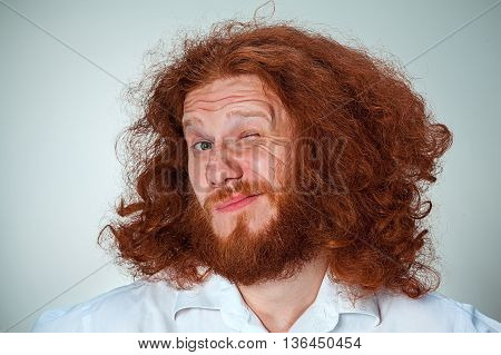 The young man with long red hair looking at camera screwing up his eyes