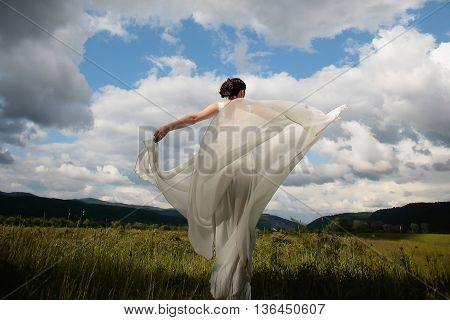 Beautiful bride stands in white wedding dress in wind on grassy valley on mountain scene background