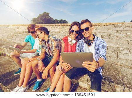 friendship, leisure, summer, technology and people concept - group of smiling friends with tablet pc computer and headphones sitting outdoors