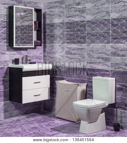 Inside of fashionable bathroom in purple and gray color - toilet and sink
