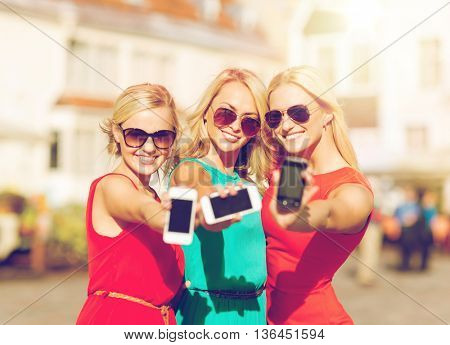 holidays and tourism, modern technology concept - beautiful blonde girls with smartphones in the city